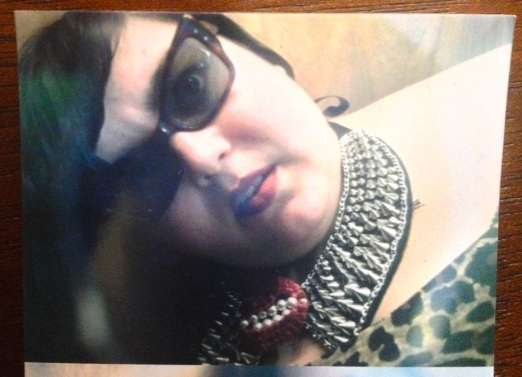 Photo booth image of me with sunglasses on, peering at the lens sideways. More detailed view of boxy vintage cat eye glasses and spiked collar necklace with mouth brooch.