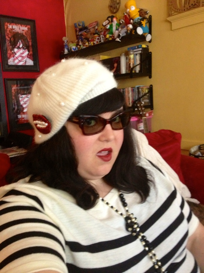 Me, a fat light skinned Latina fat femme, giving open mouthed sassy face in a shot that ends in the middle of my torso. I am wearing a cream knit dress with black stripes on the sleeves and chest, as well as a long black and white faux pearl beaded vintage necklace which is knotted. On my hair I am wearing a cream knit beret studded with intermittent pearls. On the beret is my Sequined red mouth brooch with pearl teeth. I am wearing pointy and square-ish vintage tortoise shell colored cat's eye sunglasses and a dark merlot lipstick.
