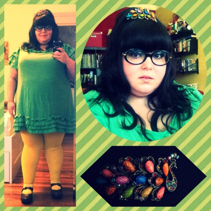 Me, a light skinned Latina woman who is fat, a size US 24-30. I'm wearing blue eyeshadow, peach lipstick and wide blue oval glasses. My hair is in a pigtail Peggy Bundy-esque bouffant with a jeweled peacock hair clip above my bangs. I'm wearing a Kelly green mini shift dress with ruffles at the sleeves and hem, with yellow trggings underneath. My shoes are black chunky Mary Janes with silver buttons.